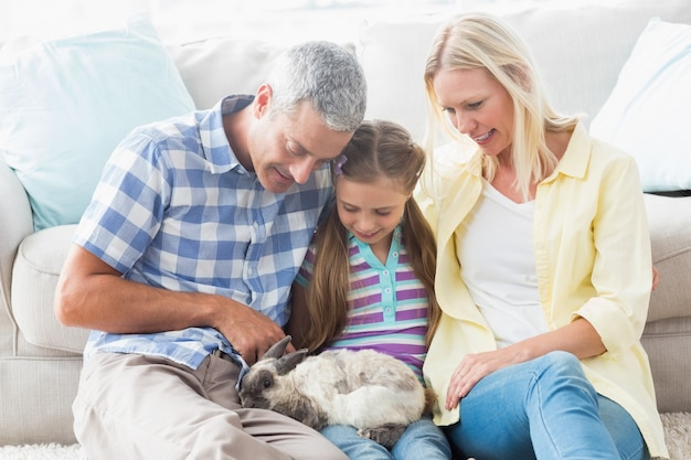Parents et fille jouant avec le lapin à la maison