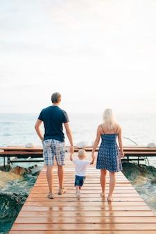 Les parents avec une fille à la mer papa et maman tiennent le