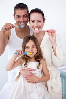 Parents et fille nettoient leurs dents dans la salle de bain