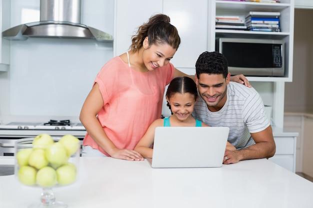 Parents, fille, utilisation, ordinateur portable, cuisine