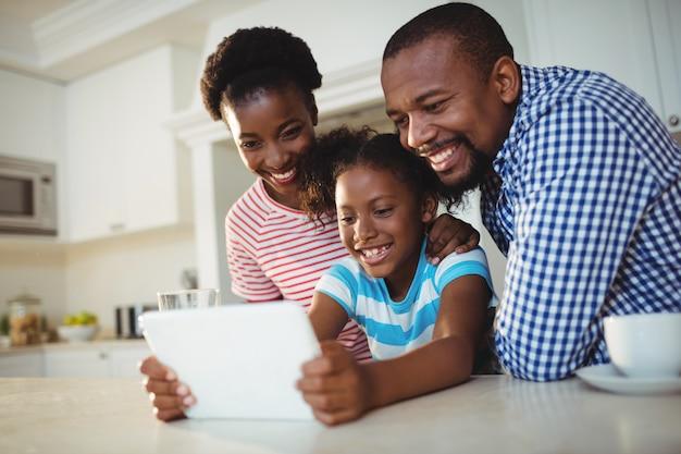 Parents, fille, utilisation, tablette numérique, dans, cuisine