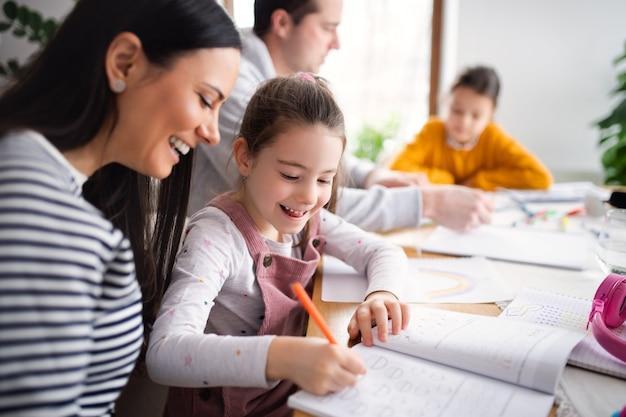 Parents avec des filles écolières à l'intérieur à la maison, apprentissage à distance.