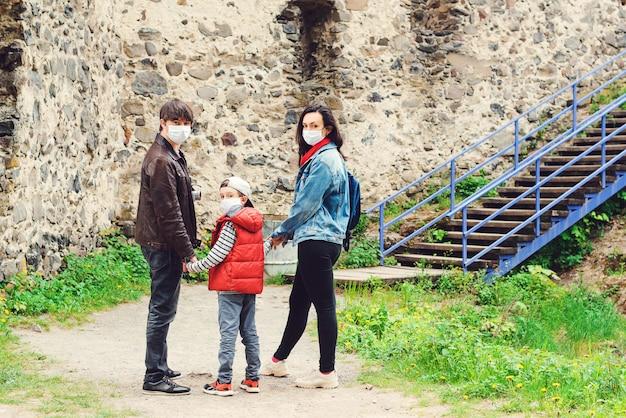 Parents avec fils portant des masques à l'extérieur. voyage en famille au vieux château. quarantaine face au coronavirus.