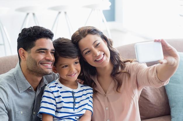 Parents et fils prenant un selfie depuis un téléphone portable dans le salon
