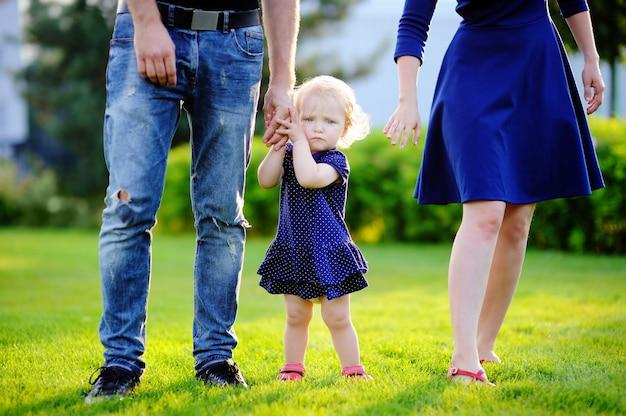 Parents heureux: jeunes parents avec leur fille douce enfant en bas âge dans un parc ensoleillé.
