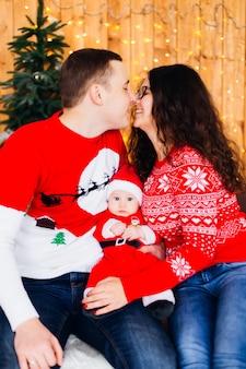 Les parents heureux veulent s'embrasser près de l'arbre de noël et les murs sont décorés de guirlandes et entre eux un fils en costume de père noël regarde l'objectif de la caméra