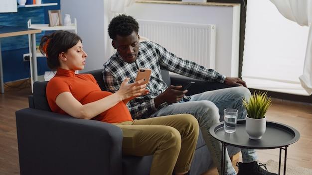 Parents interraciaux assis dans le salon attendant un enfant