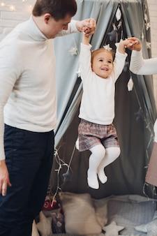 Parents jouant avec leur fille. décorations de noël.