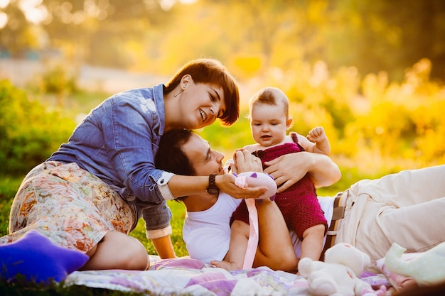 Les parents jouent avec la petite fille sur la couverture dans les rayons du soleil du soir