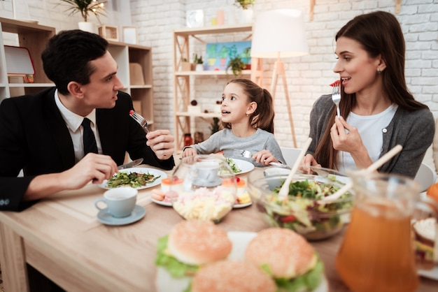 Parents avec leur fille réunis à table