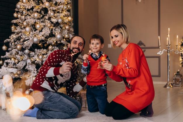 Les parents et leur petit fils en pull rouge s'amusent avec des oranges assis devant un sapin de noël