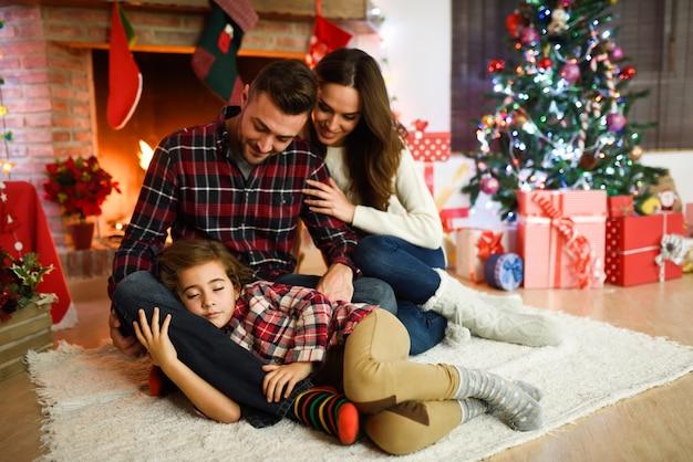 Les parents avec leur petite fille endormie dans leur salon