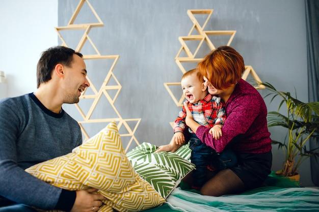 Les parents et leur petite fille jouent avec des oreillers sur le sol