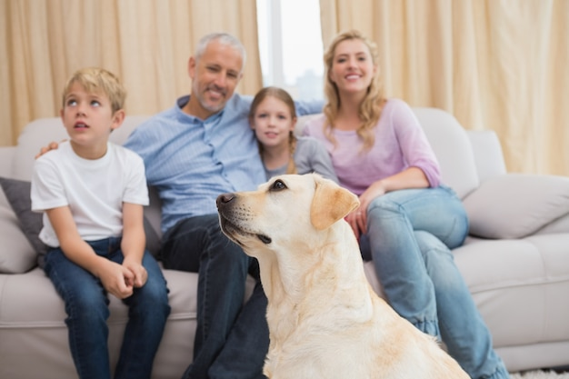Les parents et leurs enfants sur le canapé avec chiot