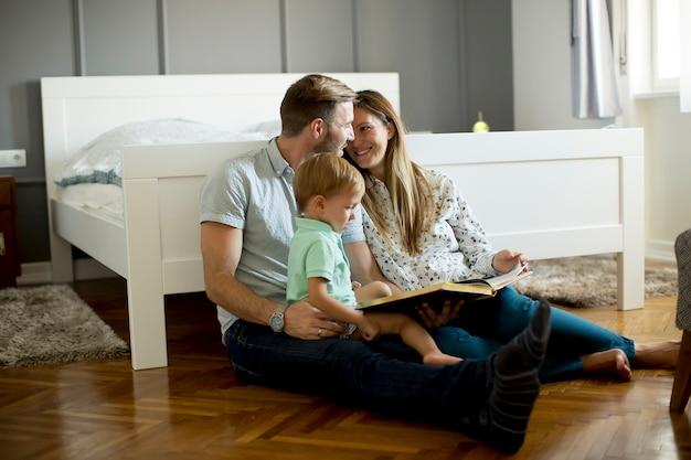 Les parents lisent un livre au petit garçon et s'amusent sur le tas dans la chambre