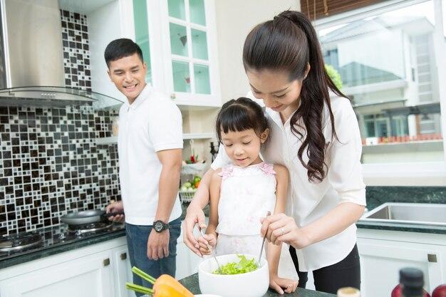 Les parents nourrissent leurs enfants à manger des légumes