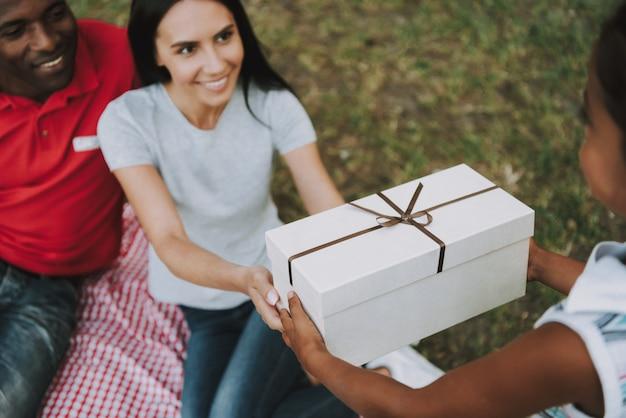 Les parents offrent un cadeau en bois à une petite fille.