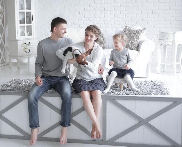 Parents et petite fille jouant avec un chien