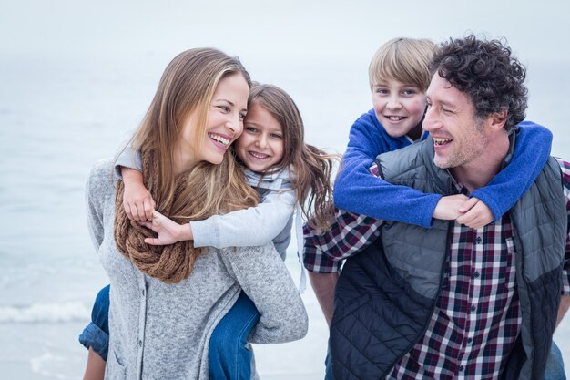 Parents portant des enfants à la plage