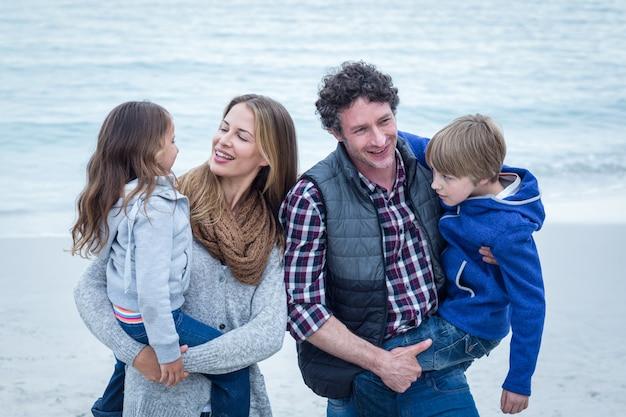 Parents portant des enfants tout en profitant de la plage