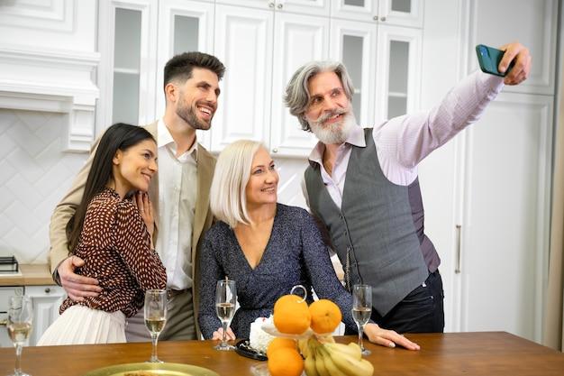 Parents positifs et jeune couple en tenue de soirée prenant un selfie ou faisant un appel vidéo sur smartphone