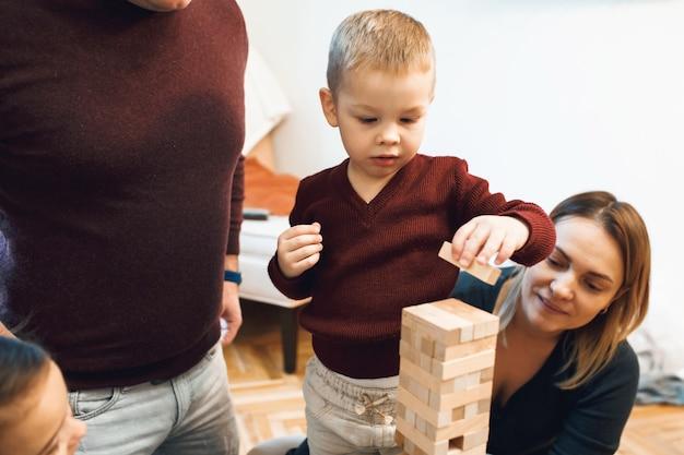 Les parents de race blanche jouant jenga avec leur fils vêtu d'un pull rouge et d'un jean blanc