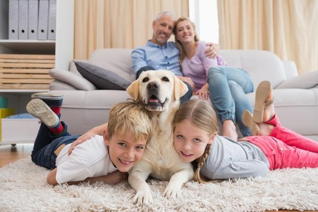 Parents regardant les enfants sur le tapis avec labrador