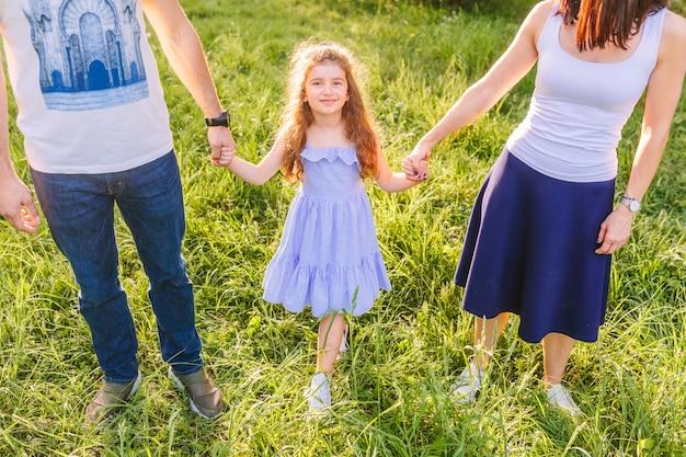 Parents avec sa fille, main dans la main dans le parc