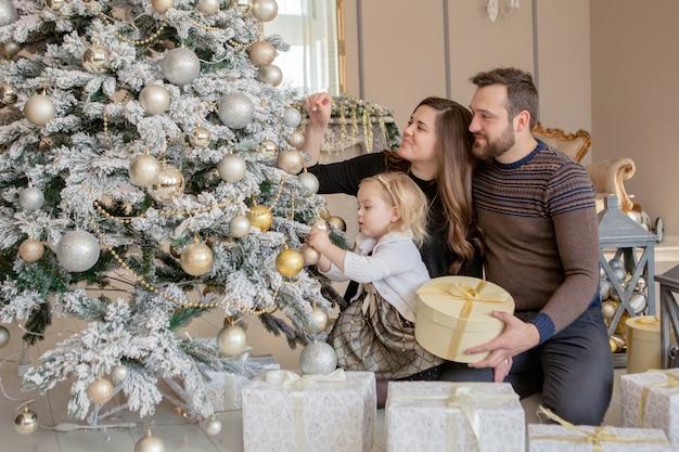 Les parents et sa petite fille décorer le sapin de noël avec des jouets et des guirlandes