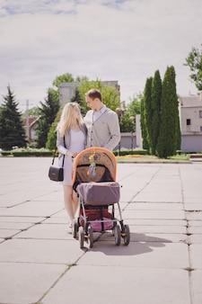 Les parents se promènent une poussette de bébé