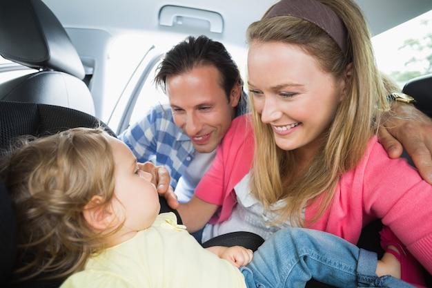 Parents sécurisant un bébé sur le siège auto