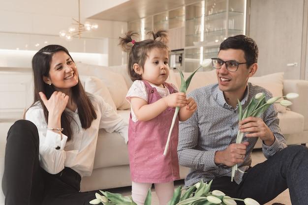 Les parents sont assis sur le canapé avec l'enfant. un enfant joyeux renifle une tulipe. journée en famille à la maison