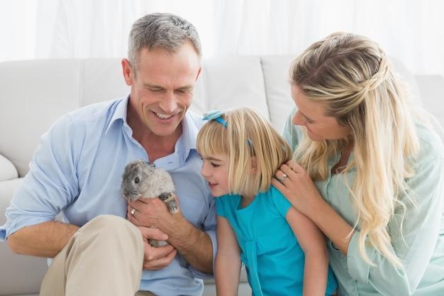 Parents souriants et fille assise avec le lapin ensemble