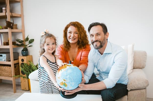 Parents souriants et fille tenant le globe, planifier des vacances.