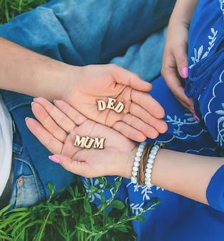 Parents tenant dans la main des lettres qui forment des mots de maman et de papa
