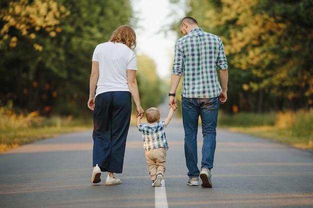 Les parents tenant leur petit fils marchent sur une route