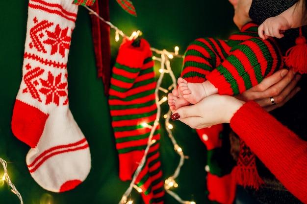 Les parents tiennent les pieds des enfants devant une guirlande lumineuse