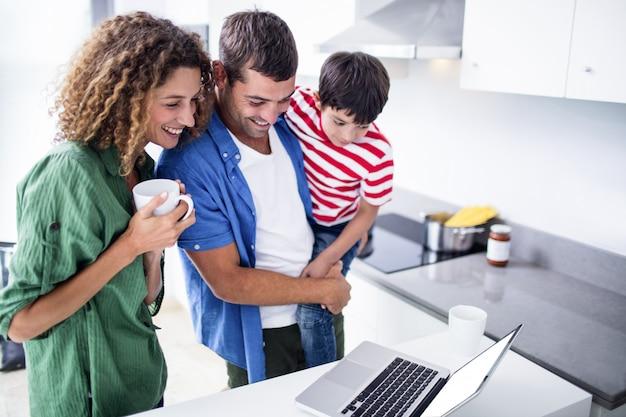 Parents utilisant un ordinateur portable avec fils dans la cuisine