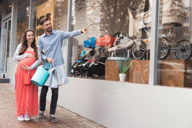 Les parents viennent au centre commercial et choisissent des choses pour leur futur enfant.