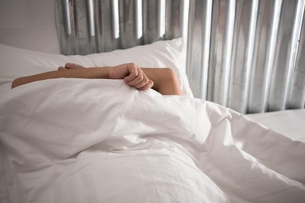 Paresse de l'homme asiatique qui dort encore sur le lit dans la chambre le matin, le temps de se réveiller.
