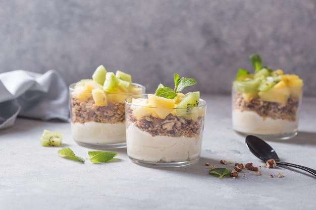 Parfait au yogourt fait maison avec granola, kiwi, ananas et noix dans un verre pour un petit déjeuner sain sur fond de béton