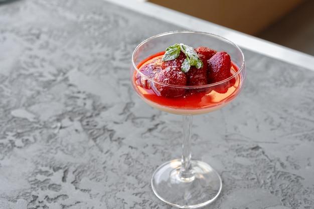 Parfait aux fraises fraîches dans une tasse en verre sur une surface grise