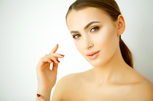 Parfait jeune mannequin avec une peau saine, des cheveux brillants et des mains manucurées. jeune beauté, traitement du visage et concept de cosmétologie
