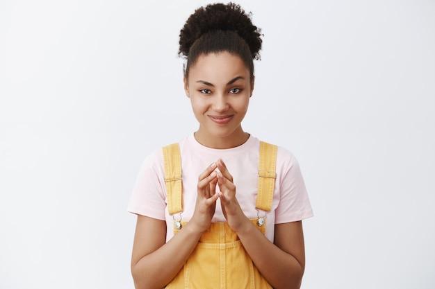 Parfait. portrait de femme stratège maléfique afro-américaine intelligente et créative, souriant et pointant les doigts tout en ayant un excellent plan, se réjouissant avant qu'il ne se réalise sur un mur gris
