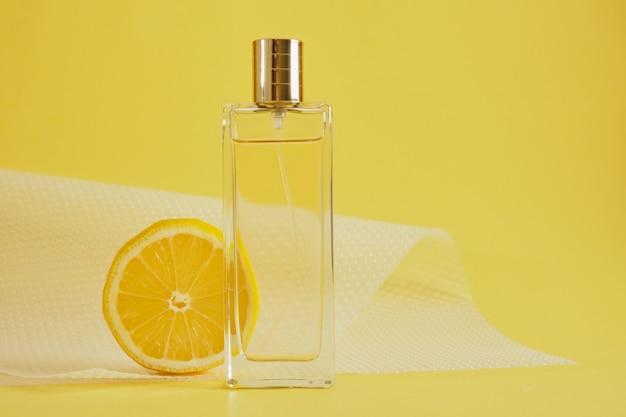 Parfum d'agrumes, parfum au concept de parfum de citron, tranche de citron et bouteille de parfum sur l'espace de copie de fond jaune