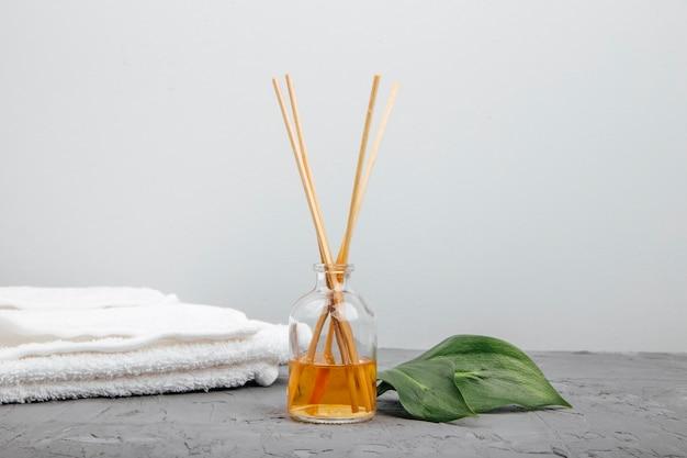 Parfum d'ambiance liquide avec des bâtons d'arôme dans une bouteille en verre