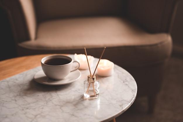 Parfum d'ambiance liquide dans une bouteille en verre avec une tasse de thé