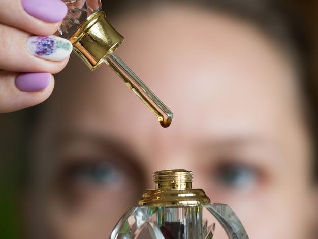 Parfum arabe oud attar ou parfums d'huile de bois d'agar dans des bouteilles en verre. une goutte de parfum sur un bâton de verre.