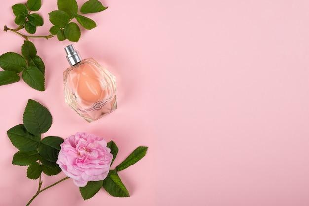 Parfum au parfum de rose sur fond rose avec espace de copie.