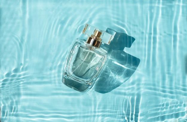 Parfum de bouteille transparent dans l'eau bleue avec des ombres.